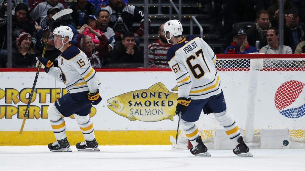 Buffalo Sabres center Jack Eichel, left, raises his stick after scoring an empty-net tally as left wing Benoit Pouliot skates in to congratulate Eiche