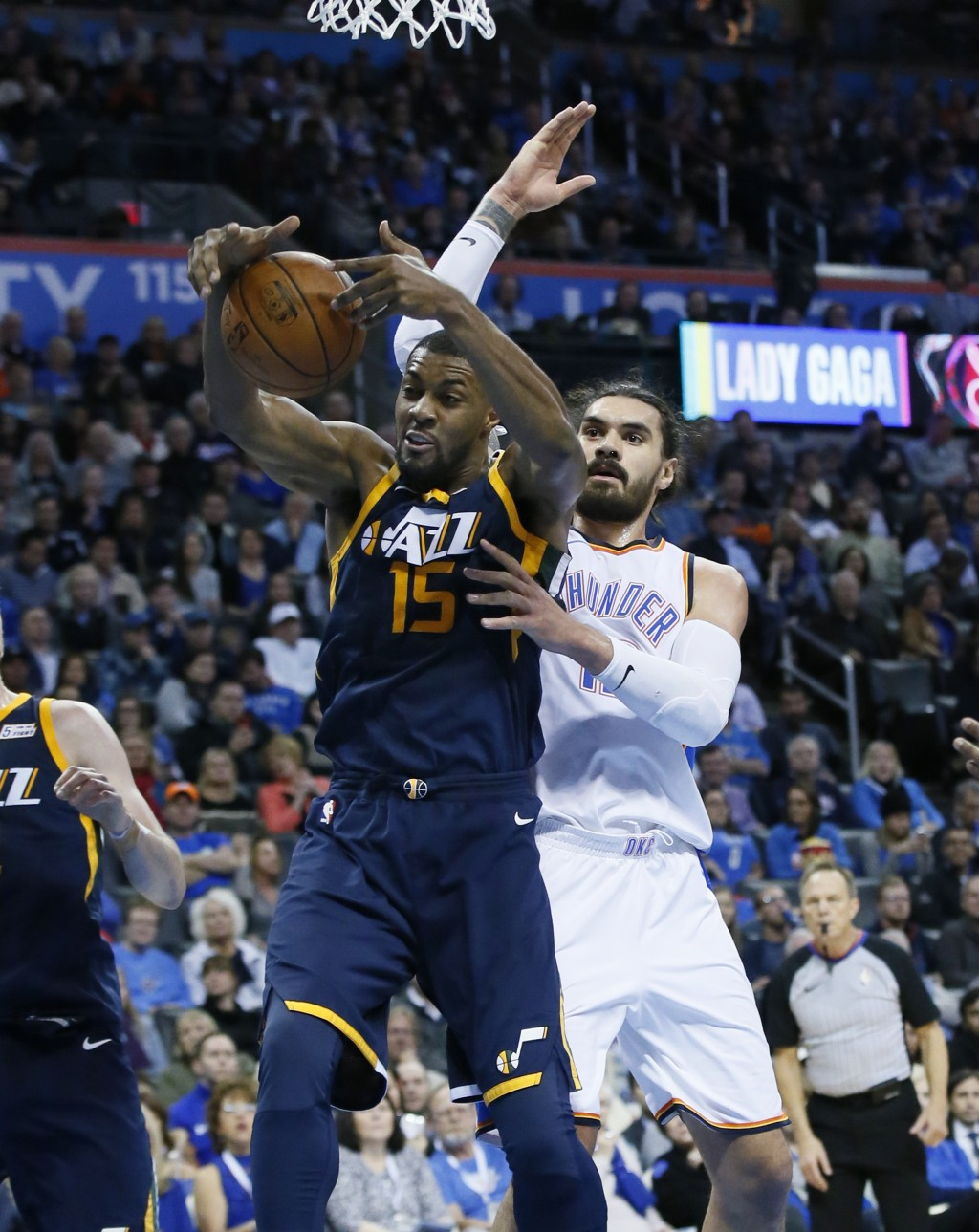 Utah Jazz forward Derrick Favors (15) grabs a rebound in front of Oklahoma City Thunder center Steven Adams, right, in the second quarter of an NBA ba