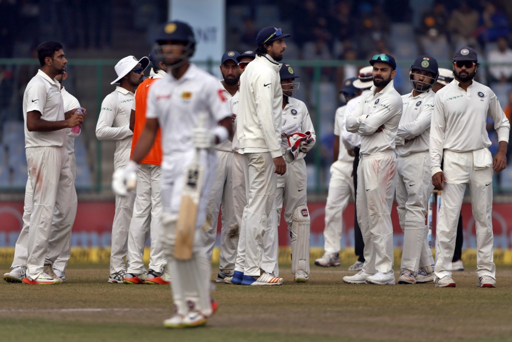 India's Ravichandran Ashwin, left, celebrates with teammates the dismissal of Sri Lanka's captain Dinesh Chandimal during the fifth day of their third