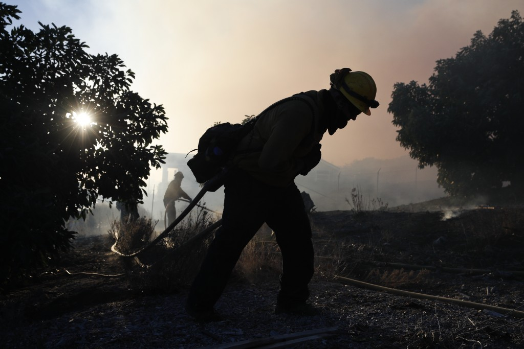 A firefighter pulls a water hose as a wildfires continues to burn Tuesday, Dec. 5, 2017, in Santa Paula, Calif. Raked by ferocious Santa Ana winds, ex