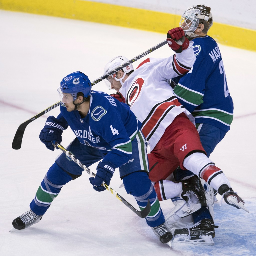 Carolina Hurricanes center Derek Ryan (7) falls to the ice while trying to get a shot past Vancouver Canucks defenseman Michael Del Zotto (4) and Canu
