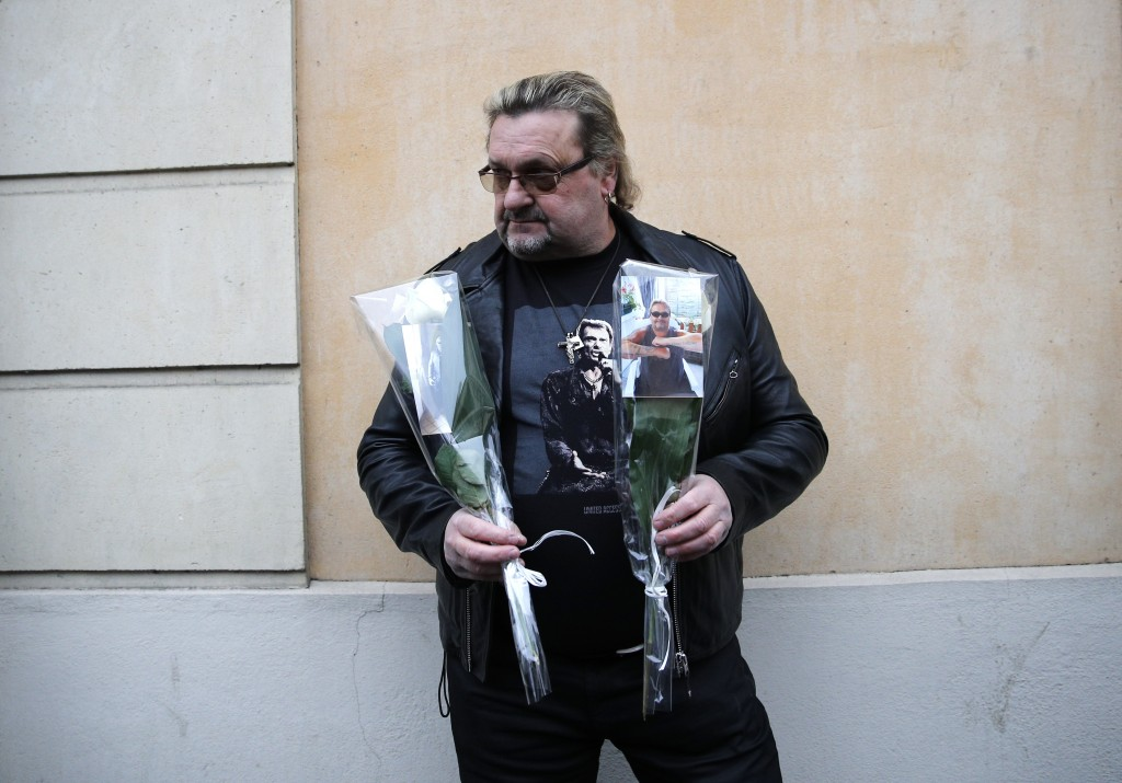 Johnny Hallyday's fan Yves Buisson hold flowers outside Hallyday's house in Marnes-la-Coquette, outside Paris, Wednesday, Dec.6, 2017. Johnny Hallyday