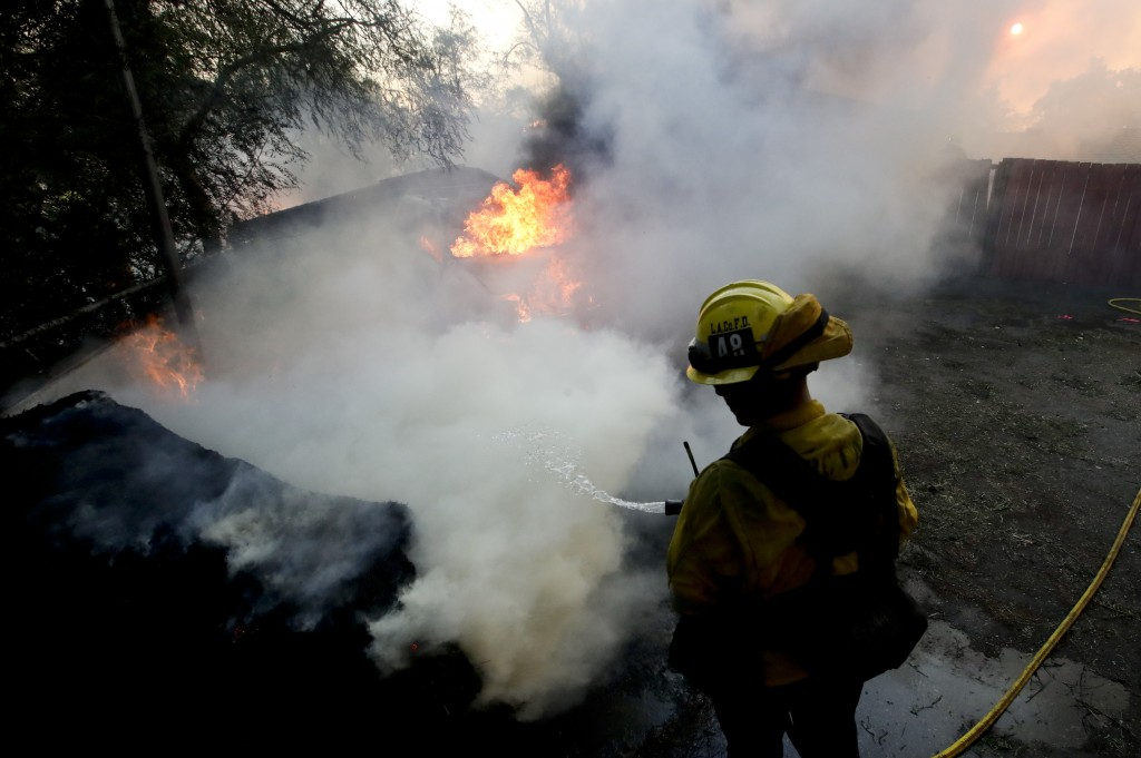 A Los Angeles County firefighter puts water on a burning car during a wildfire in the Lake View Terrace area of Los Angeles Tuesday, Dec. 5, 2017. For
