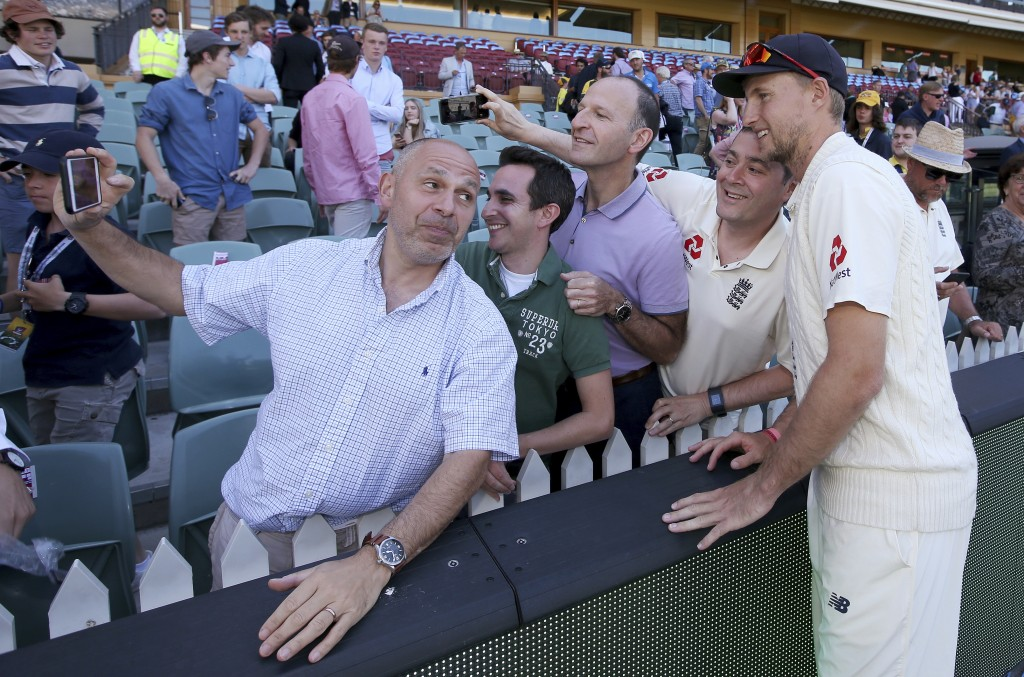 England's Joe Root, right, poses for a photo with fans at the end of their Ashes cricket test match against Australia in Adelaide, Wednesday, Dec. 6,