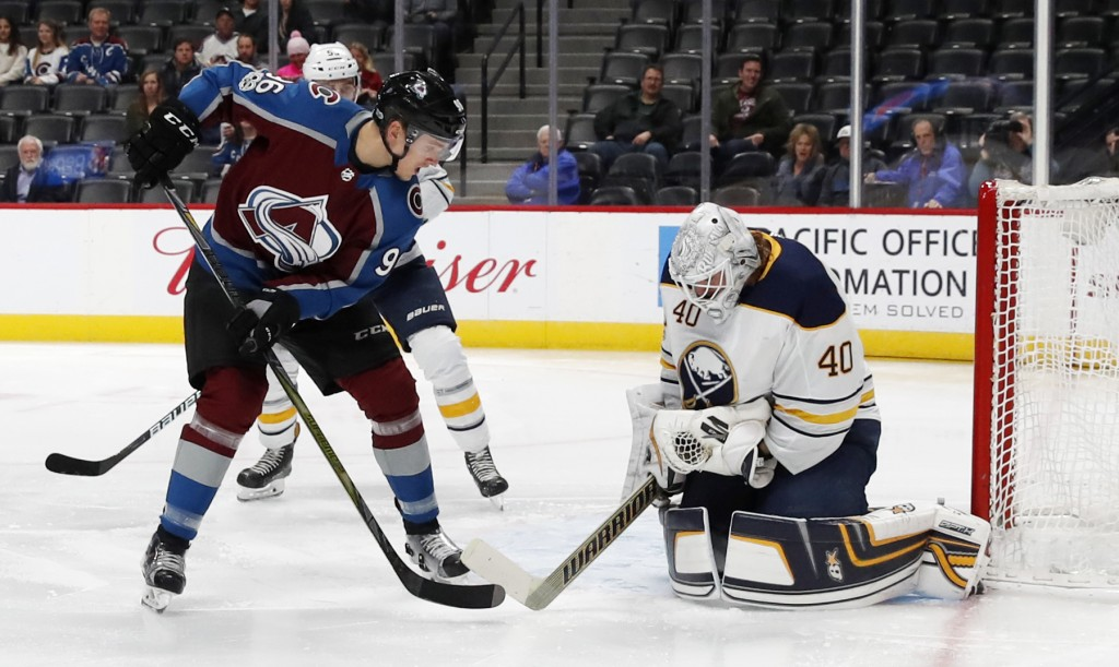 Buffalo Sabres goalie Robin Lehner, right, makes a save off a shot of the stick of Colorado Avalanche right wing Mikko Rantanen, of Finland, in the fi