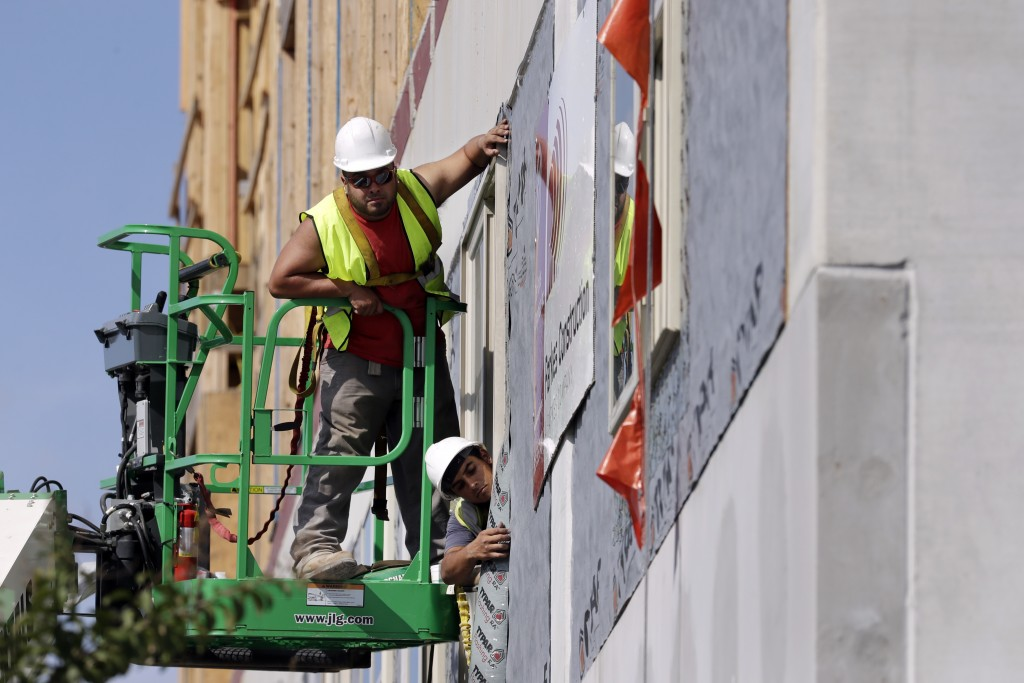 In this Friday, Oct. 6, 2017, photo, workers build an apartment and retail complex in Nashville, Tenn. On Wednesday, Dec. 6, 2017, the Labor Departmen