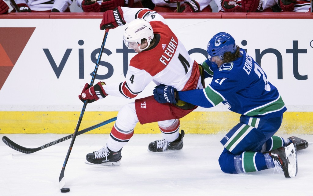 Vancouver Canucks left wing Loui Eriksson (21) competes for control of the puck with Carolina Hurricanes defenseman Haydn Fleury (4) during the third