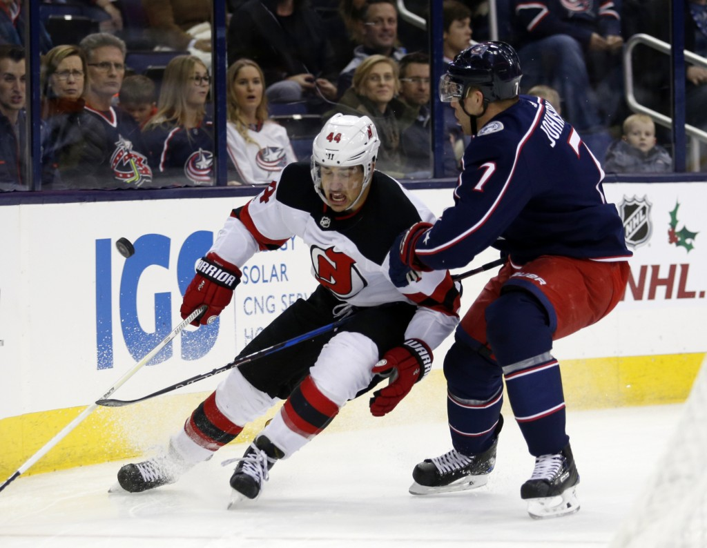 New Jersey Devils forward Miles Wood, left, chases the puck against Columbus Blue Jackets defenseman Jack Johnson during the first period of an NHL ho