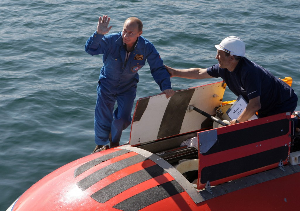 FILE- In this file photo taken on Saturday, Aug. 1, 2009, Russian Prime Minister Vladimir Putin, left, climbs aboard a mini-submarine before his desce