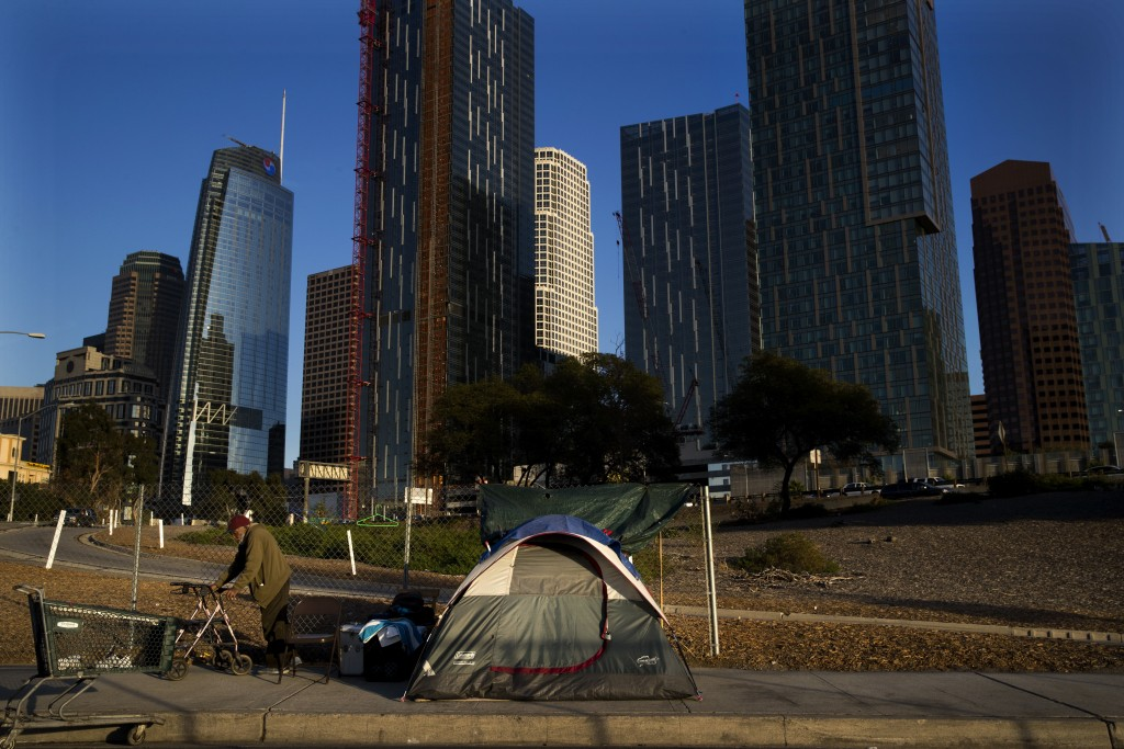 A homeless man, who declined to give his name, is dwarfed by skyscrapers Monday, Dec. 4, 2017, in Los Angeles. The U.S. Department on Housing and Urba