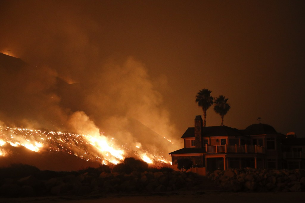 A wildfire threatens homes as it burns along the 101 Freeway Tuesday, Dec. 5, 2017, in Ventura, Calif. Raked by ferocious Santa Ana winds, explosive w