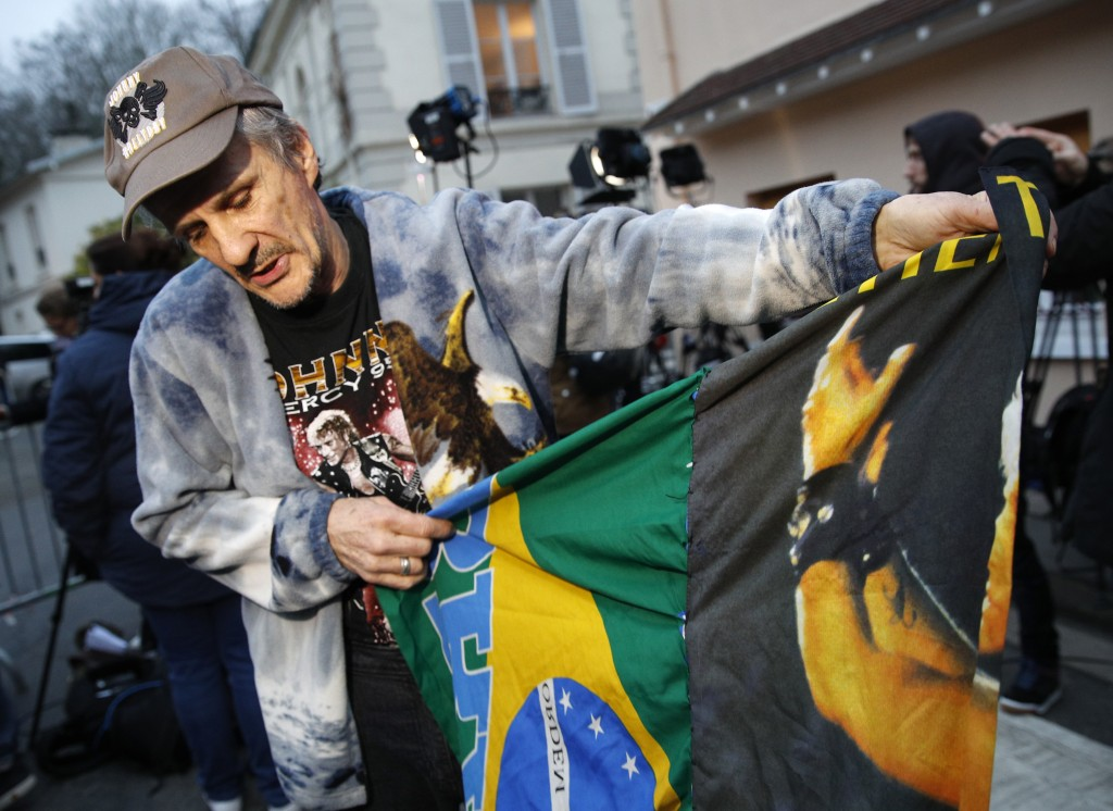 Jose, from Brazil, a fan of Johnny Hallyday, displays a flag he bought during a concert, outside Hallyday's house in Marnes-la-Coquette, outside Paris