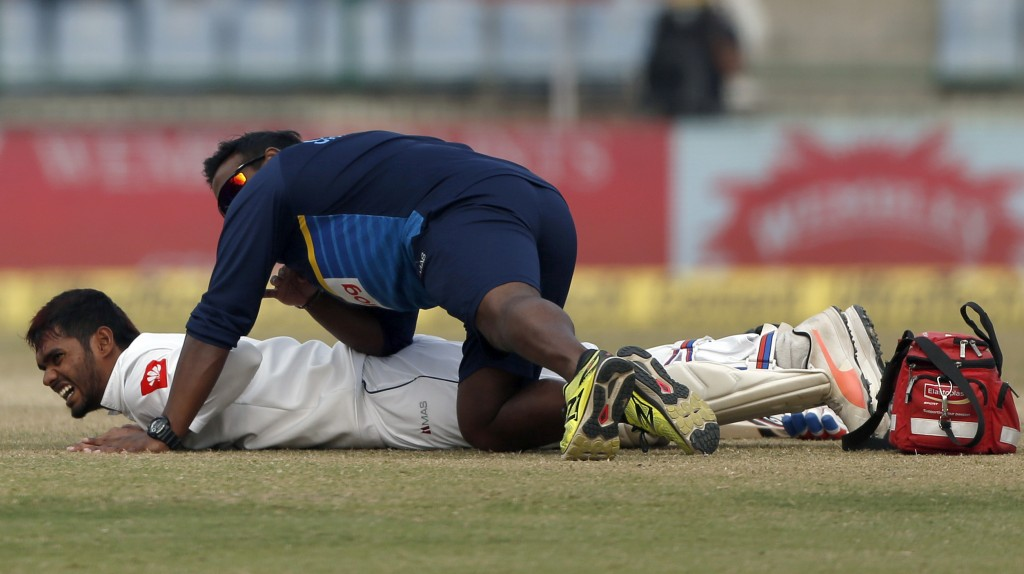 Sri Lankan team physiotherapist attends to Dhananjaya De Silva during the fifth day of their third test cricket match against India in New Delhi, Indi