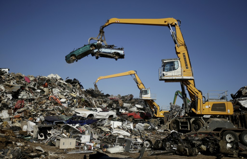 In this Friday, Dec. 1, 2017, photo, workers place old automobiles on a scrap pile to be shredded at Midwest Scrap Management in Kansas City, Mo. The