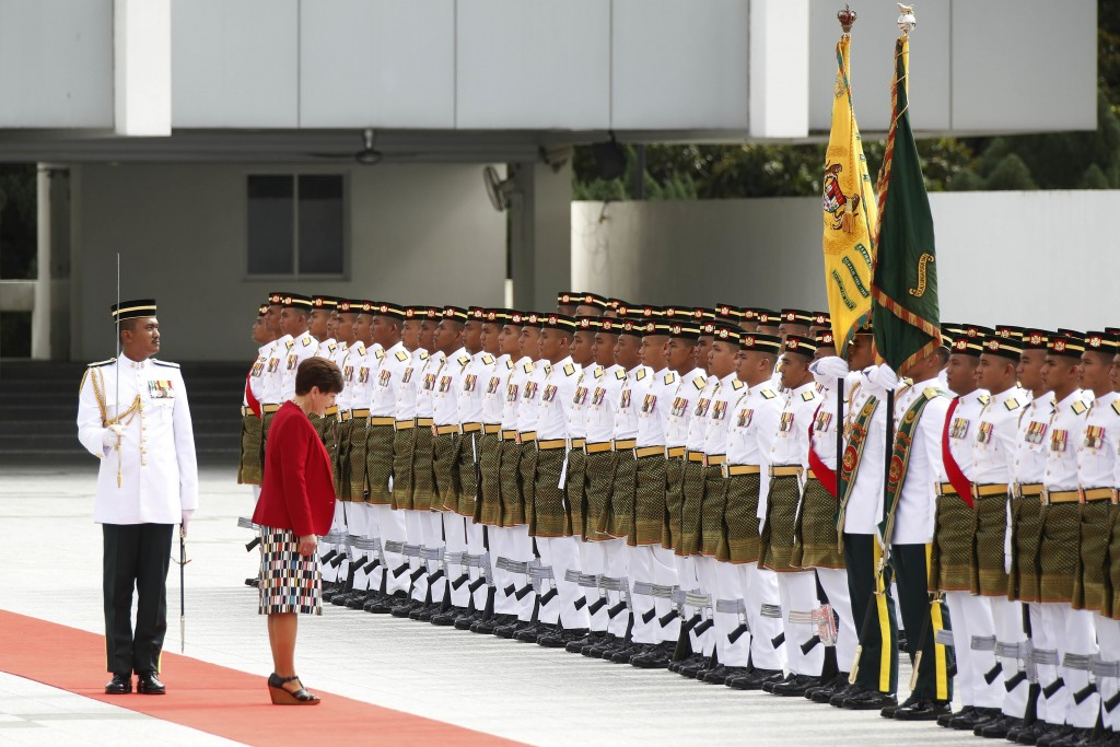 New Zealand's Governor-General Dame Patsy Reddy, second left, bows to honor guard during a welcome ceremony at parliament house in Kuala Lumpur, Malay