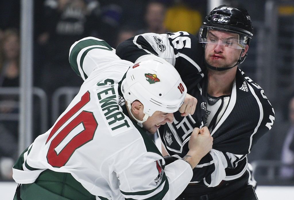 Los Angeles Kings defenseman Kurtis MacDermid, right, fights Minnesota Wild right wing Chris Stewart during the first period of an NHL hockey game in