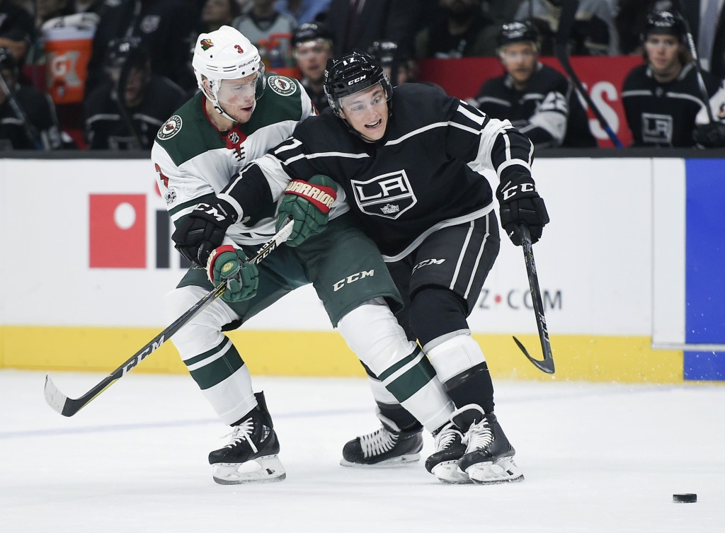 Los Angeles Kings center Jonny Brodzinski, right, works for the puck against Minnesota Wild center Charlie Coyle during the first period of an NHL hoc