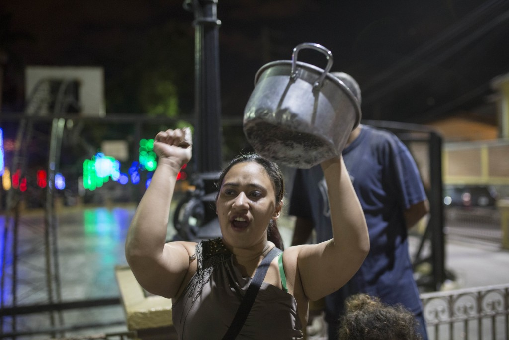 An anti-government demonstrator bangs a cooking pot in protest during a government imposed dawn-to-dusk curfew in Tegucigalpa, Honduras, late Tuesday,