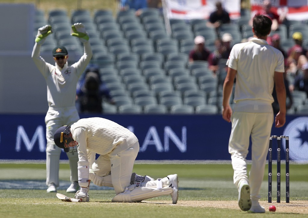 England's Craig Overton, center, falls to his knees after being hint by a delivery from Australia's Pat Cummins, right, during the fifth day of their
