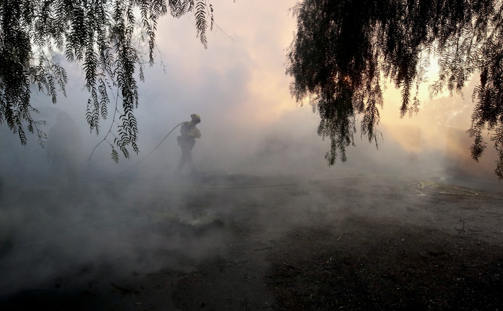 A Los Angeles County firefighter pulls a firehose in the smoke from a wildfire in the Lake View Terrace area of Los Angeles, Tuesday, Dec. 5, 2017. (A