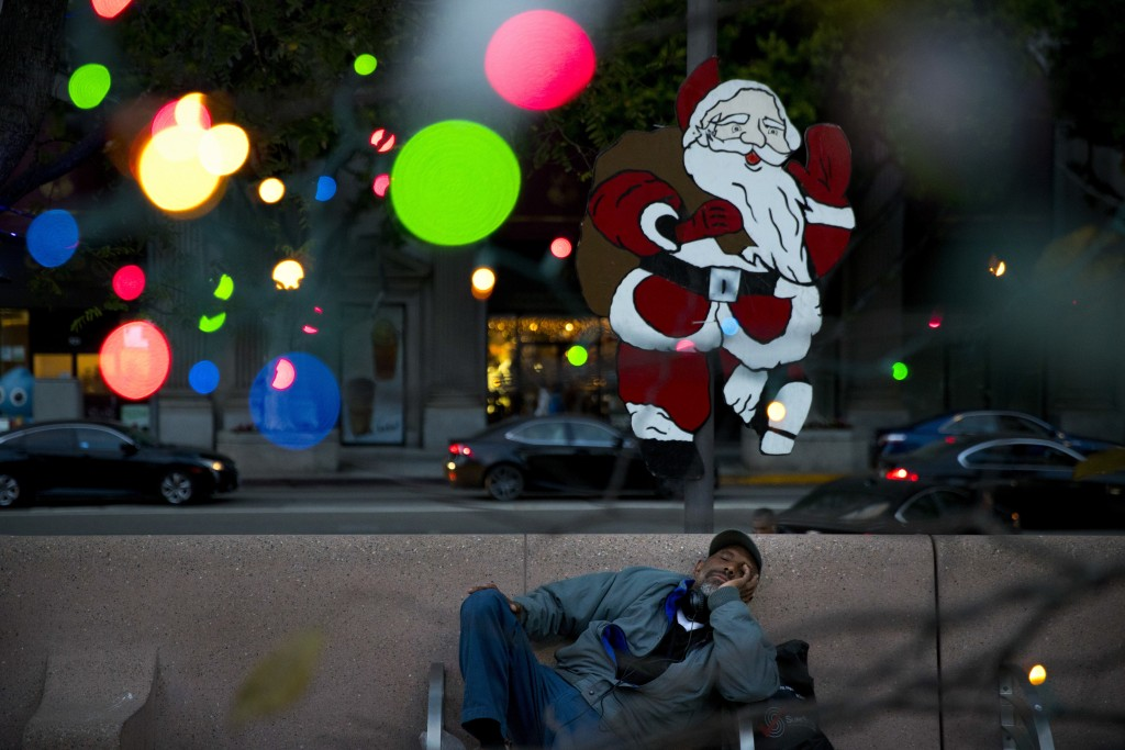 Homeless man Alonzo Harrison, 47, takes a nap on a bench at Pershing Square decorated with Christmas lights in the background on Monday, Dec. 4, 2017,