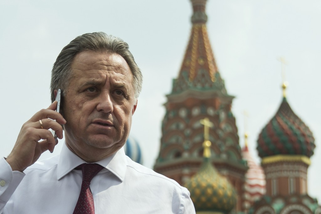 FILE - In this July 27, 2016 file photo Russia's Sports Minister Vitaly Mutko uses a mobile phone with the St.Bazil's Cathedral at the background, as