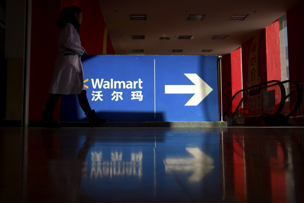 A shopper walks toward an escalator at a Walmart store in Beijing, Wednesday, Dec. 6, 2017. U.S. companies in China are seeing their sales improve but