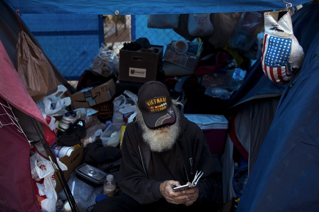 Theodore Neubauer, a 78-year-old Vietnam War veteran, who is homeless, looks at his smartphone while passing time in his tent Friday, Dec. 1, 2017, in