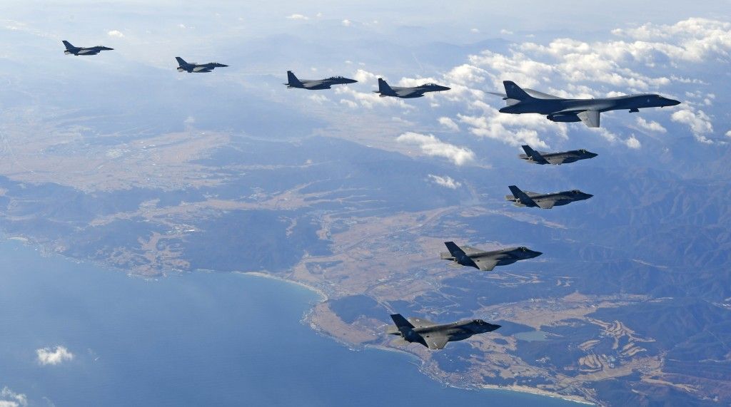 In this photo provided by South Korea Defense Ministry, U.S. Air Force B-1B bomber, right top, flies over the Korean Peninsula with South Korean fight...