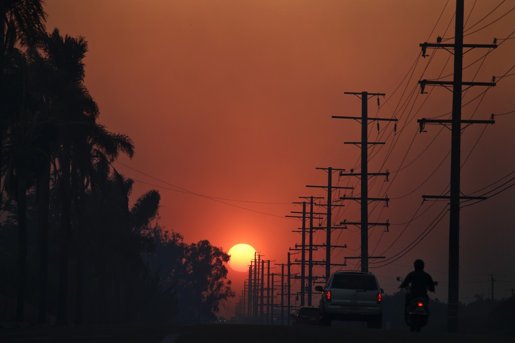 The sun is seen through thick smoke generated by a wildfire Tuesday, Dec. 5, 2017, in Santa Paula, Calif. Raked by ferocious Santa Ana winds, explosiv