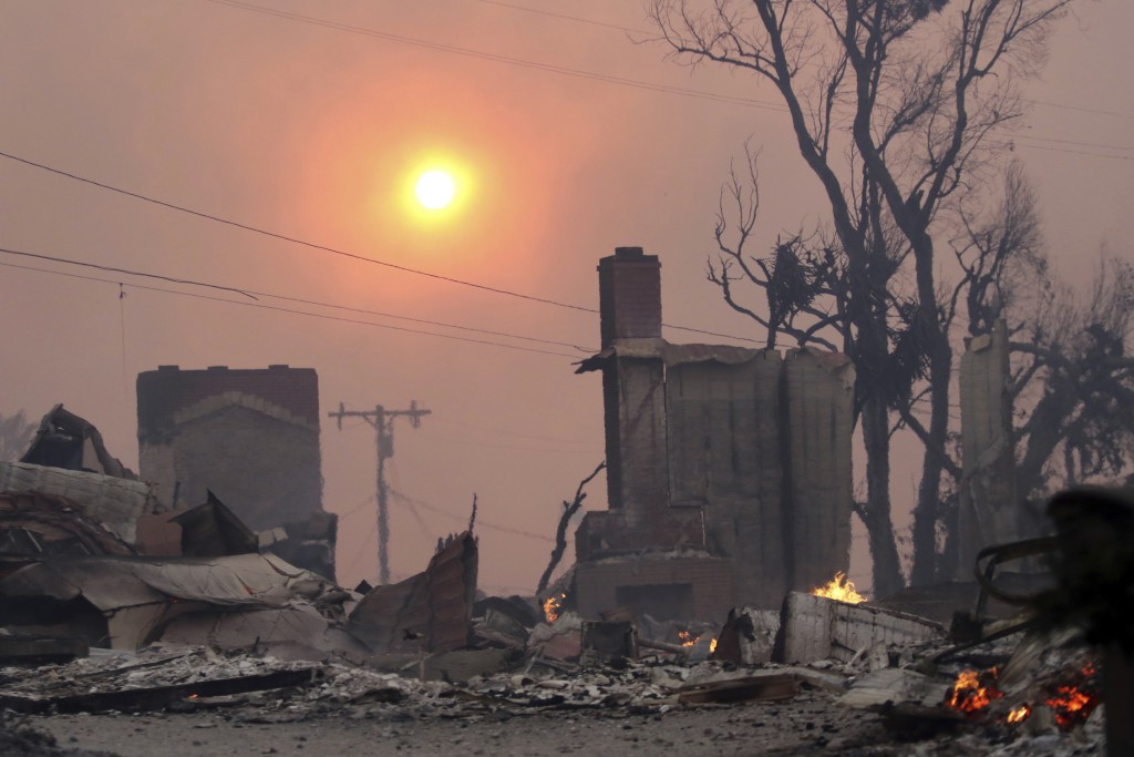 The sun breaks through dense smoke over fire-damaged structures in Ventura, Calif., Tuesday, Dec. 5, 2017. Ferocious Santa Ana winds raking Southern C