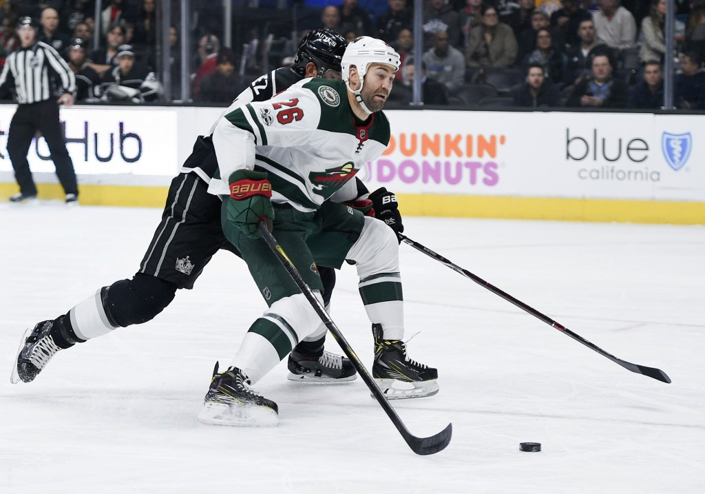 Minnesota Wild left wing Daniel Winnik, front, handles the puck under pressure from Los Angeles Kings defenseman Alec Martinez during the first period