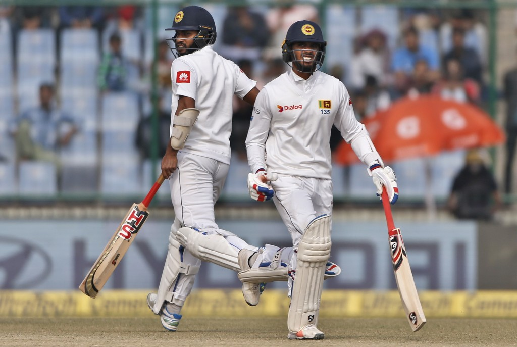 Sri Lanka's Dhananjaya De Silva, right, reacts in pain as he runs between the wickets with teammate Roshen Silva during the fifth day of their third t