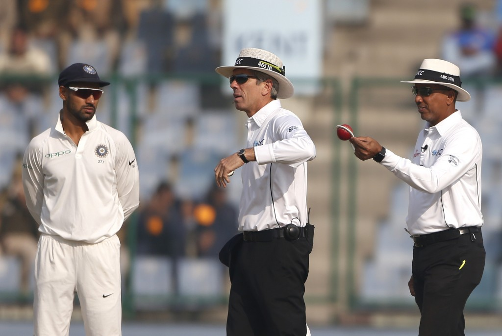 India's Shikhar Dhawan, left, watches umpire Joel Wilson, right, checking the condition of the ball before asking for a new one during the fifth day o