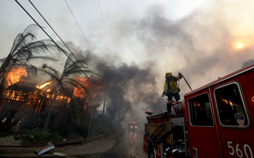 """A Los Angeles County firefighter prepares to battle a hot spot on the """"Creek Fire"""" in the Lake View Terrace area of Los Angeles, Tuesday, Dec. 5, 2017"""