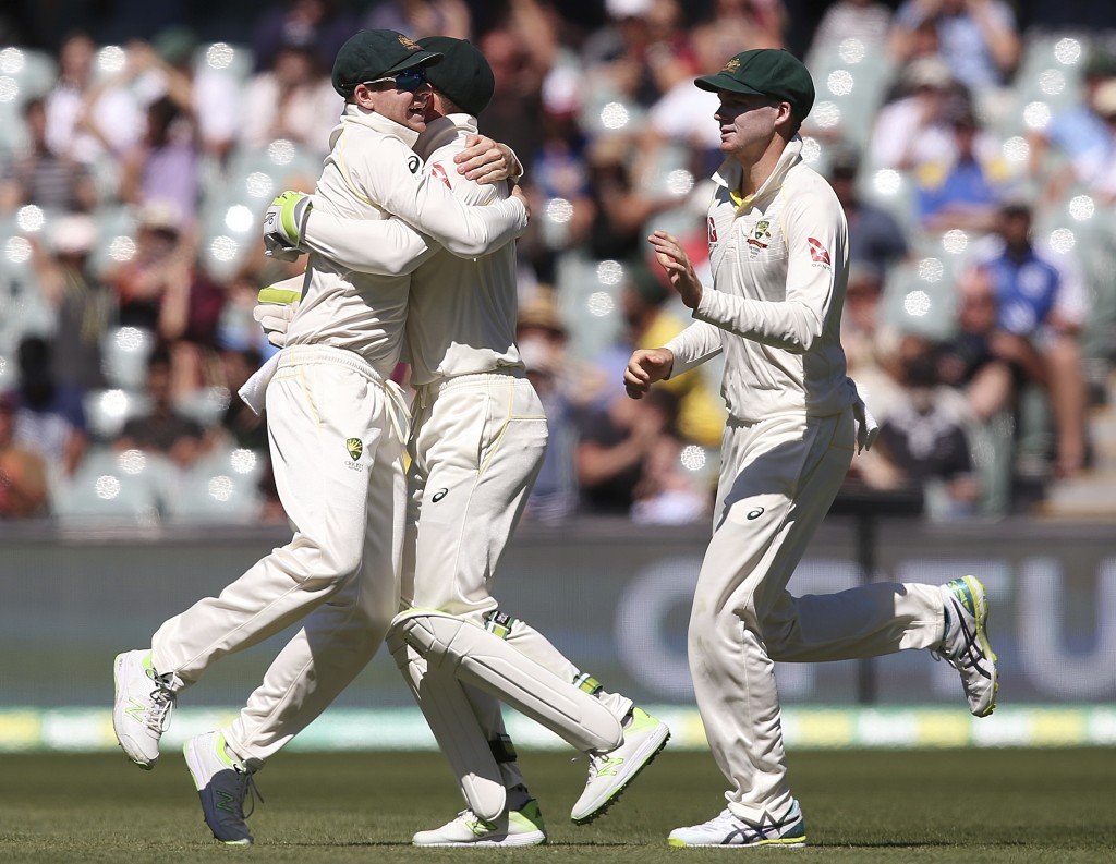 Australia's Steve Smith, left, Tim Paine and Peter Handscomb, right celebrate the fall of the last English wicket at the end of their Ashes cricket te