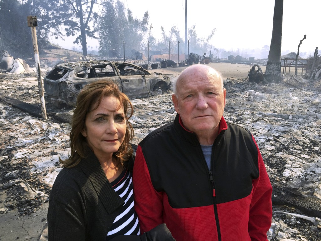 Linda and John Keasler pose for a photo in front of the ruins of their home at the Hawaiian Village Apartments, destroyed when the Thomas fire swept t