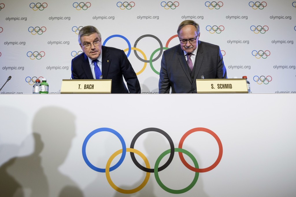 International Olympic Committee, IOC, President Thomas Bach from Germany, left, and Samuel Schmid, President of the IOC Inquiry Commission and former