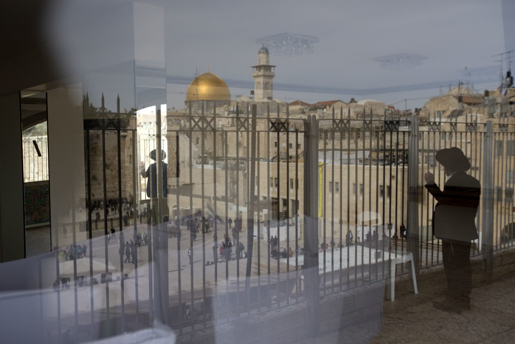 FILE - In this Monday, Feb. 1, 2016 file photo, an ultra-Orthodox Jewish man looks at the Western Wall and Dome of the Rock in the back, in Jerusalem'