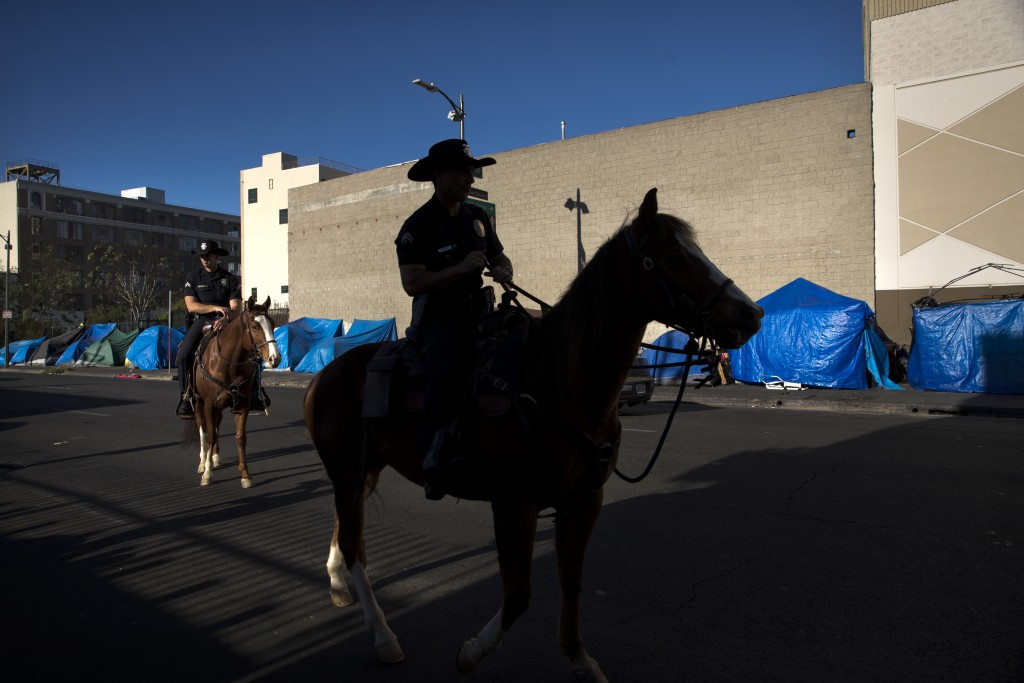 Tents belonging to homeless people are covered with tarps as Los Angeles police officers on horses patrol in the Skid Row area of downtown Los Angeles
