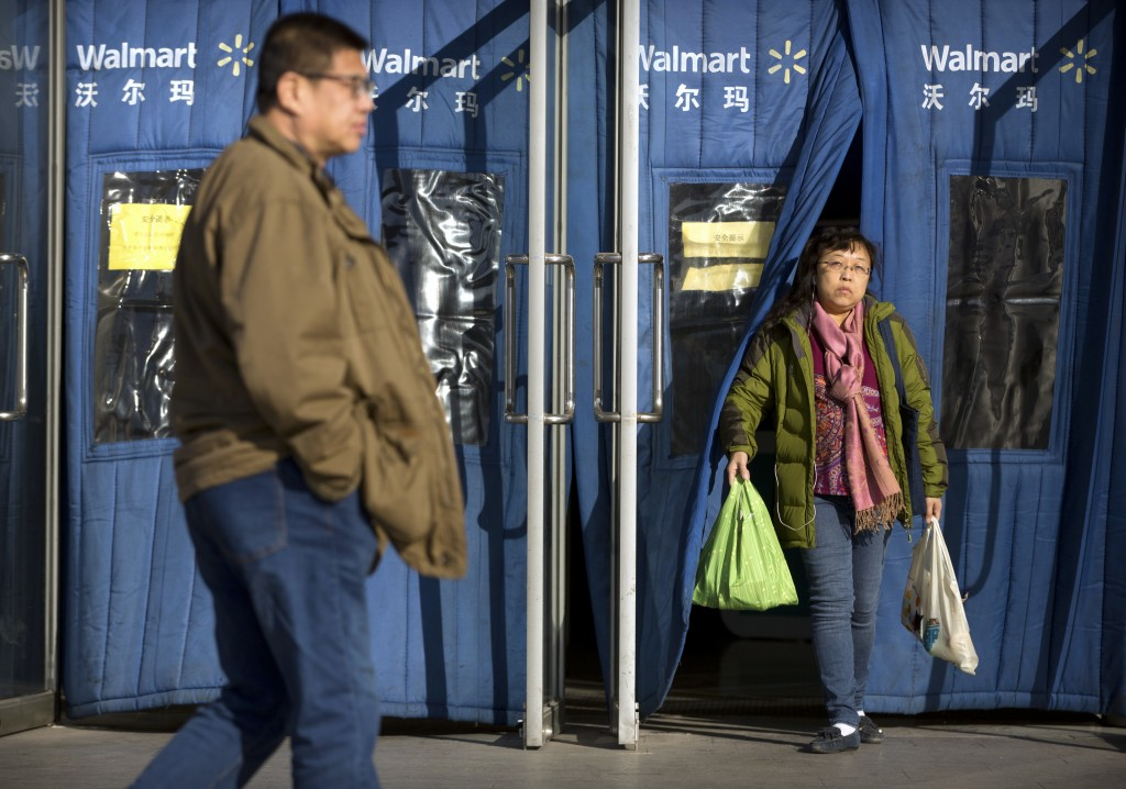 A shopper carries grocery bags as she exits a Walmart store in Beijing, Wednesday, Dec. 6, 2017. U.S. companies in China are seeing their sales improv