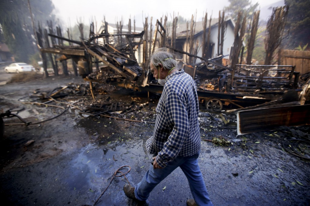 Homeowner Alan Barnard walks past the remains of his RV from a wildfire in the Lake View Terrace area of Los Angeles on Tuesday, Dec. 5, 2017. (AP Pho