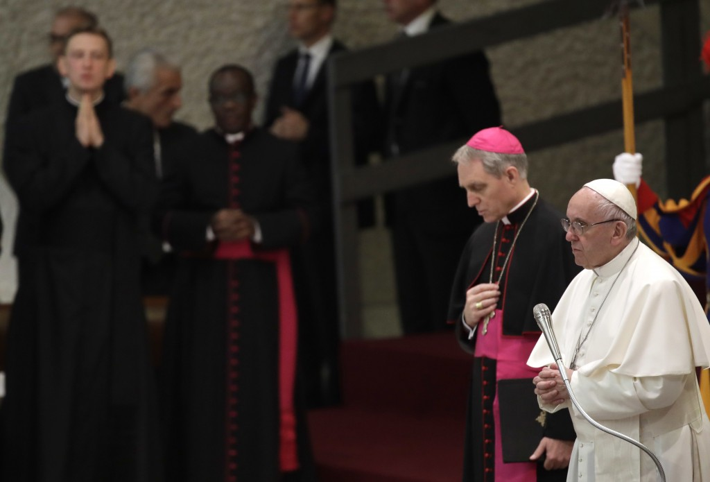 Pope Francis is flanked by Archbishop Georg Gaenswein as he prays during his weekly general audience in the Paul VI Hall at the Vatican, Wednesday, De