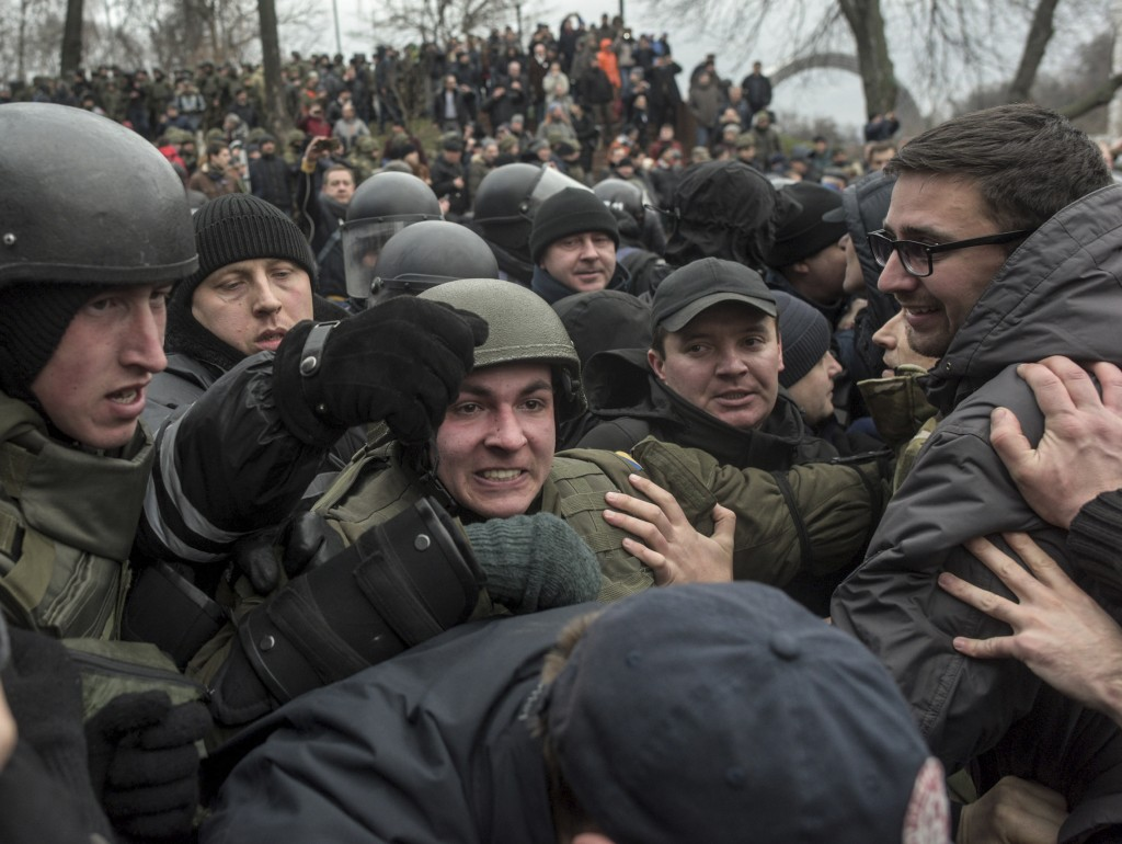 Police try to block supporters of former Georgian president Mikheil Saakashvili during a rally in Kiev, Ukraine, Tuesday, Dec. 5, 2017.  Some hundreds