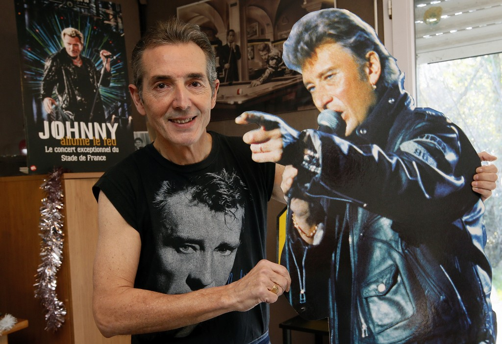 Lilian Lissalde, a fan of Johnny Hallyday poses with a promotion poster of Halliday in Anglet, southwestern France, Wednesday, Dec.6, 2017. Johnny Hal