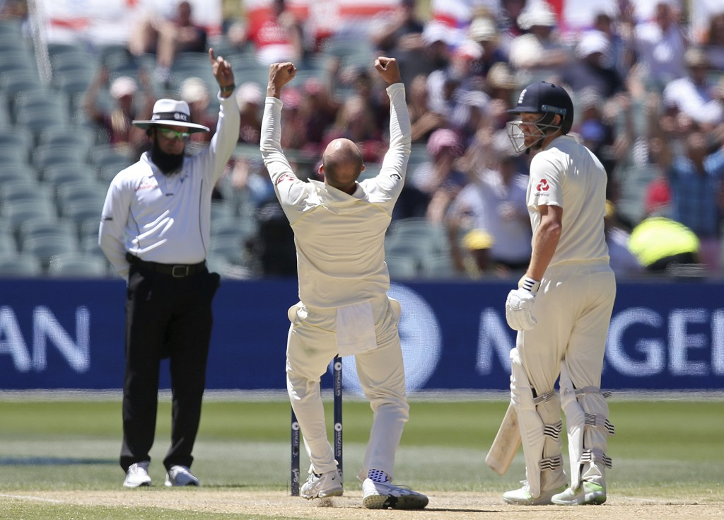 England's Jonny Bairstow, right, looks at Australia's Nathan Lyon, center, as umpire Umpire Aleem Dar gives out England's Moeen Ali during the fifth d