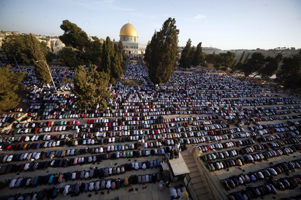 FILE - In this Sept. 24, 2015, file photo, Palestinians pray during the Muslim holiday of Eid al-Adha, near the Dome of the Rock Mosque in the Al Aqsa