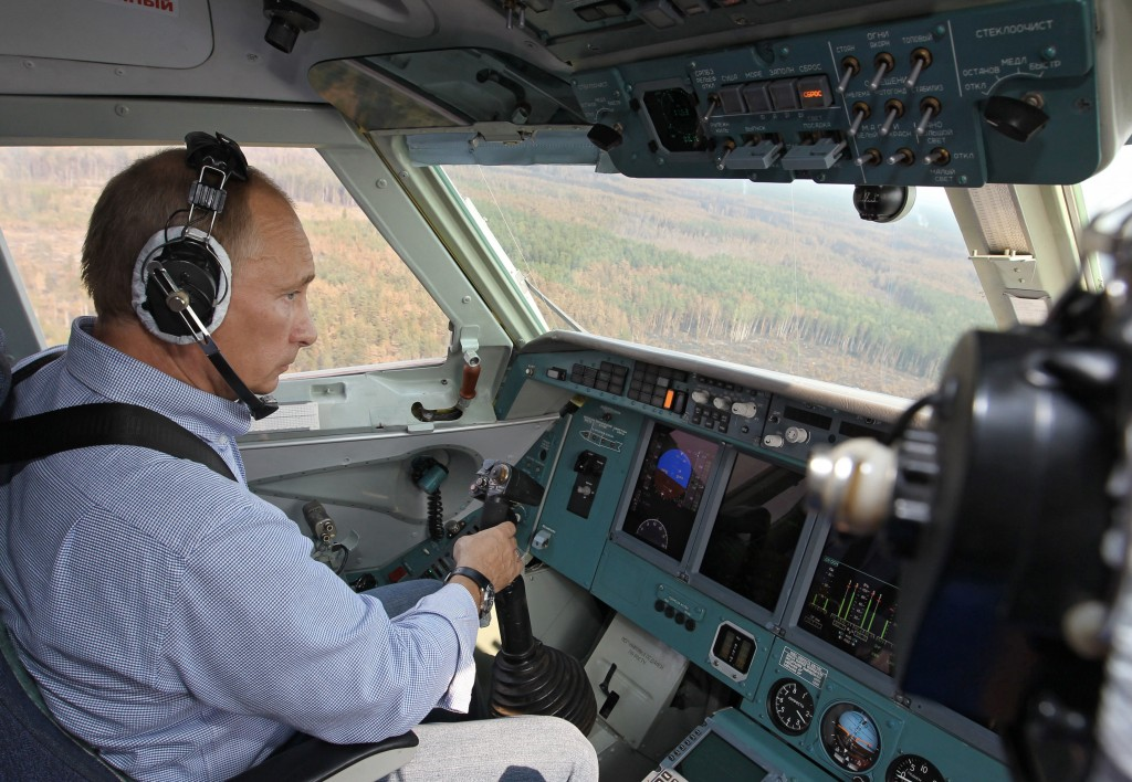 FILE- In this Tuesday, Aug. 10, 2010 file photo, then Russian Prime Minister Vladimir Putin sits in the co-pilot's seat in the cockpit of an Emergenci