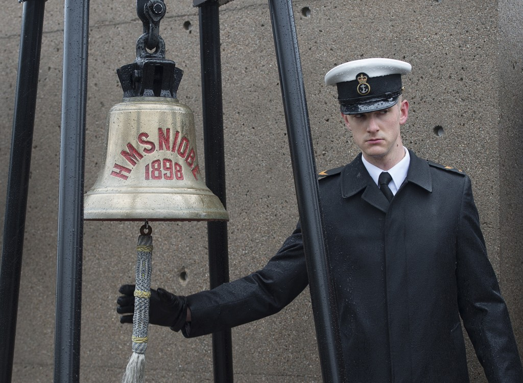 A sailor rings the bell from HMS Niobe at a ceremony to mark the 100th anniversary of the Halifax Explosion at Fort Needham Memorial Park in Halifax,