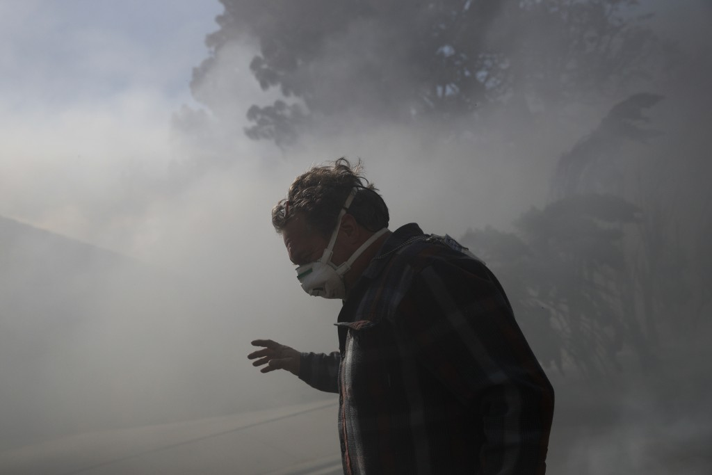 A photographer struggles as he walks through smoke from a wildfire burning near a home in Ventura, Calif., on Tuesday, Dec. 5, 2017. Ferocious winds i